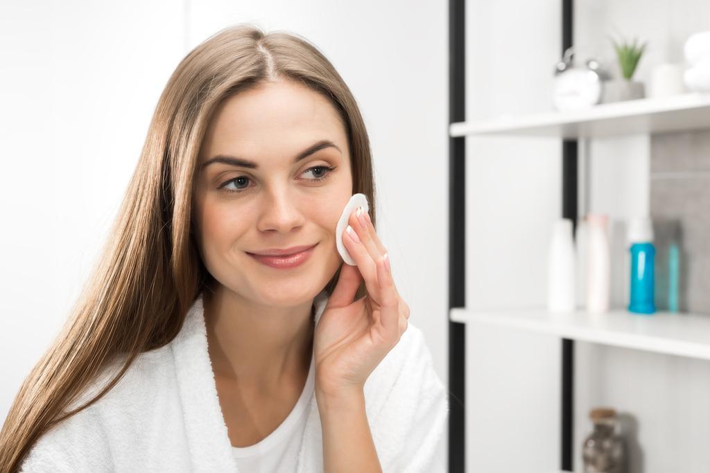 Foto e imagen de stock sin royalties de Mujer limpiando su cara con  almohadilla de algodón y mirando al espejo