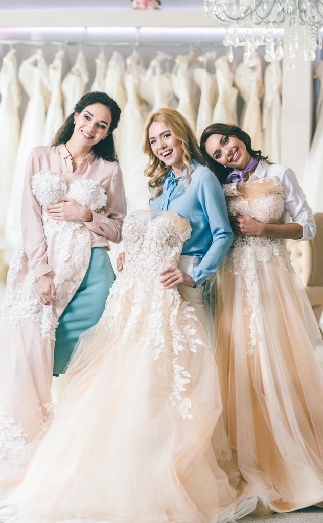 Attraktive Frauen Mit Brautkleidern Im Geschaft Fur Hochzeitsmode Lizenzfreies Foto Und Stockbild