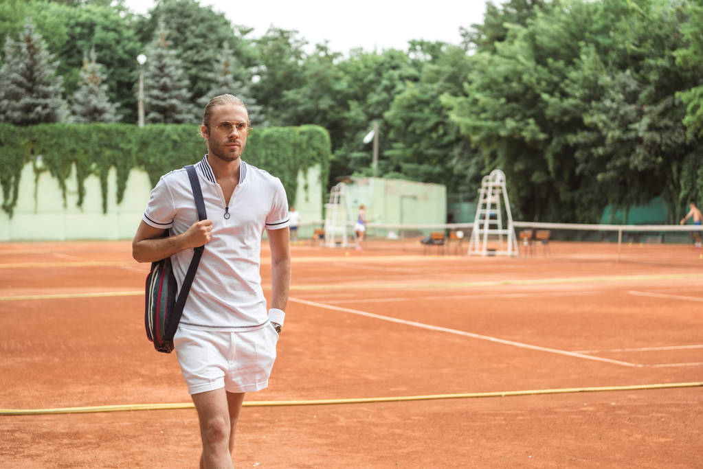 handsome tennis player after training on brown tennis court  - Photo, Image