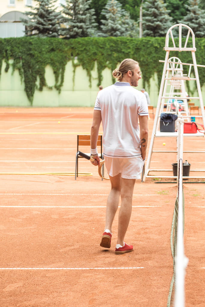 rear view of tennis player with racket on tennis court  - Photo, Image