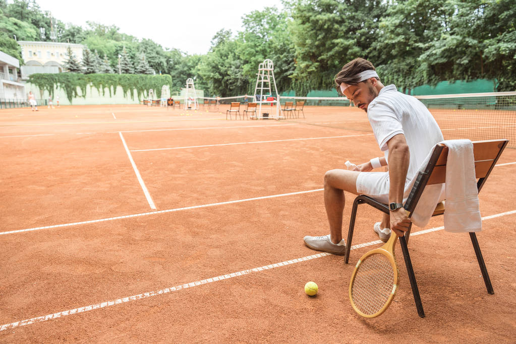 tennis player sitting on chair with tennis ball, retro wooden racket and towel on court - Photo, Image