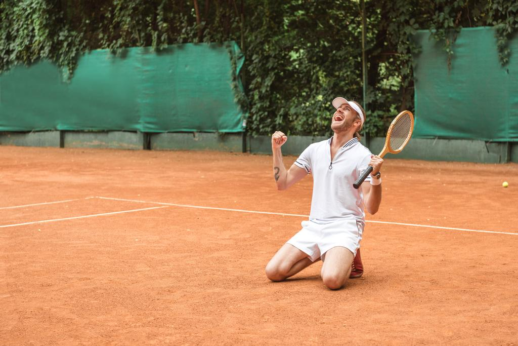 blond winner with racket celebrating and kneeling on tennis court - Photo, Image