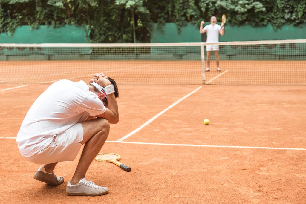 frustrated tennis player after fail on brown tennis court  - Photo, Image