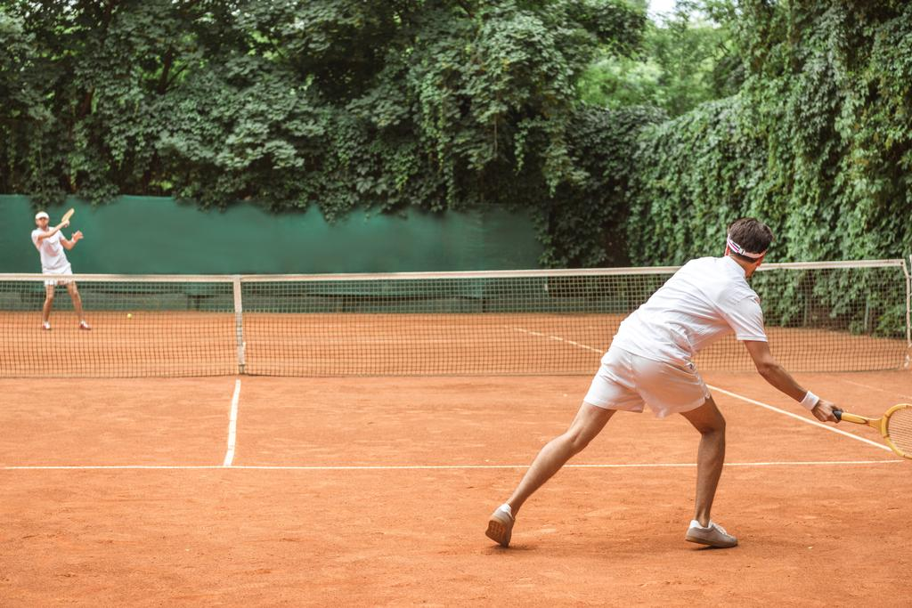 old-fashioned sportsmen playing tennis with wooden rackets on court - Photo, Image