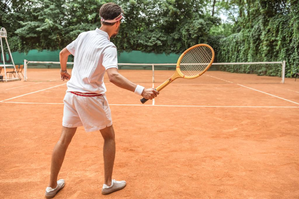 back view of tennis player with retro wooden racket on tennis court - Photo, Image