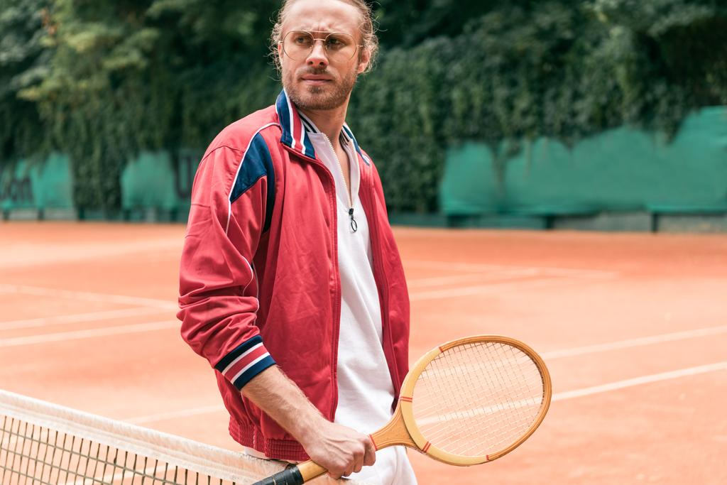 handsome man with wooden tennis racket standing at net on tennis court - Photo, Image