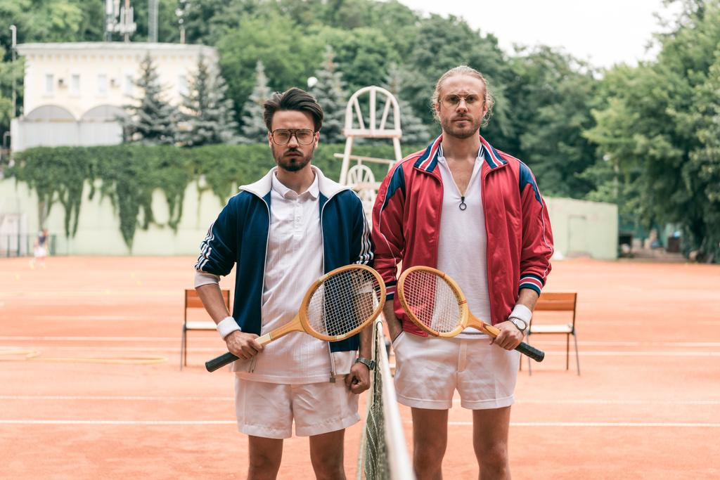 old-fashioned friends with wooden rackets posing on tennis court with net - Photo, Image