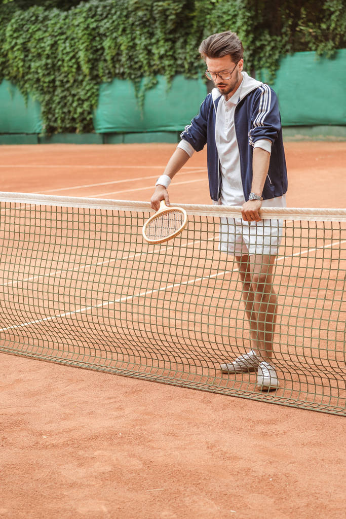 handsome retro sportsman with racket leaning on tennis net on brown court - Photo, Image