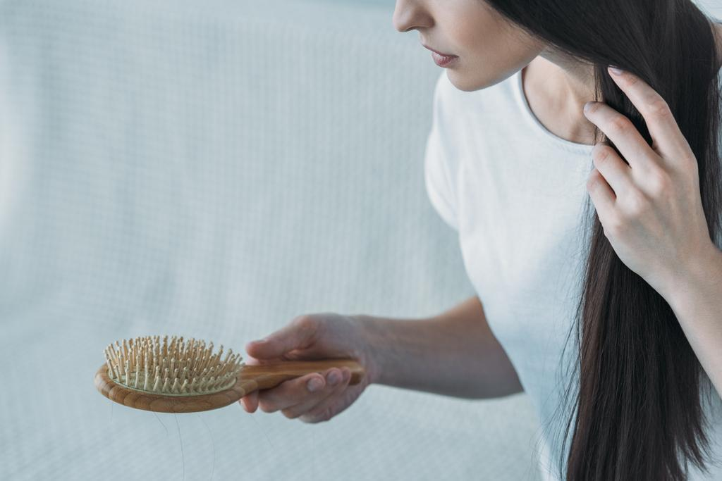 cropped shot of sad brunette woman holding hairbrush, hair loss concept - Photo, Image