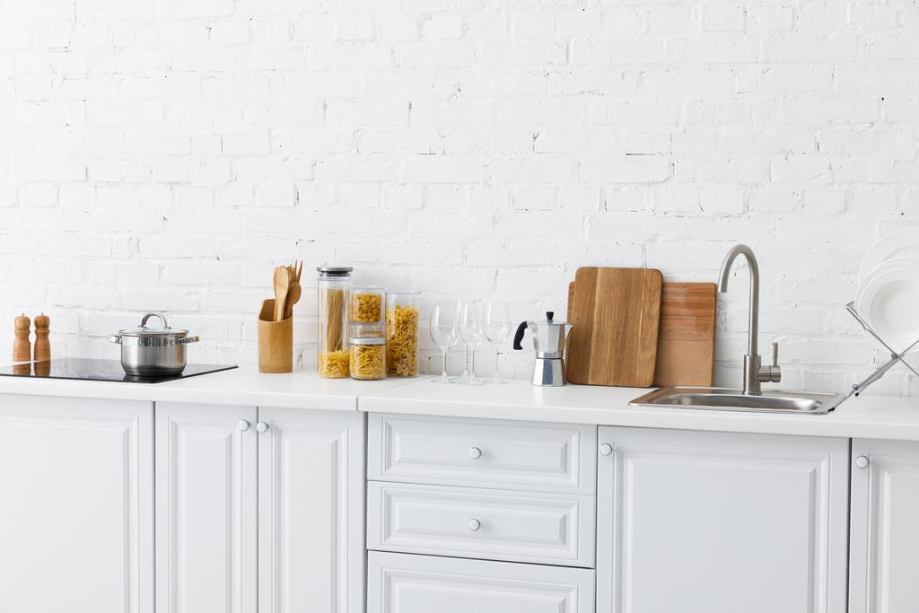 Minimalistic Modern White Kitchen Interior With Kitchenware Near Brick Wall Free Stock Photo And Image