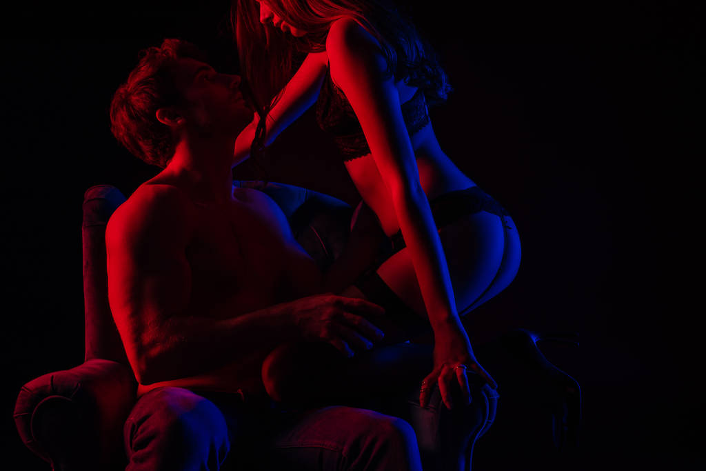 sexy woman in underwear dancing striptease to boyfriend in armchair in red light isolated on black - Photo, Image