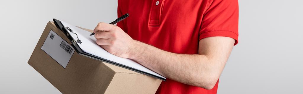 Обрезанный вид курьера, пишущего на планшете и держащего картонную коробку, изолированную на сером, панорамный снимок  - Фото, изображение