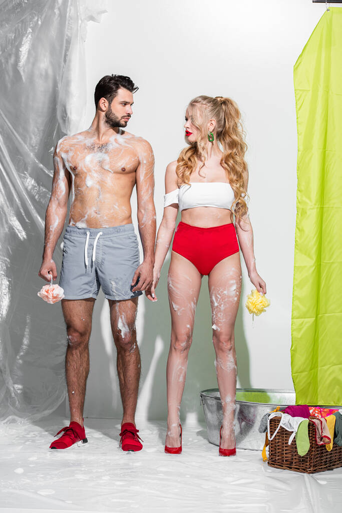 Muscl guy around sexy girls holding them Sexy Pin Up Girl Holding Wet Sponge With Soap Near Shirtless Man On White Free Stock Photo And Image