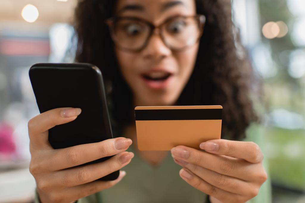 Смартфон и кредитная карта в руках изумленной девушки