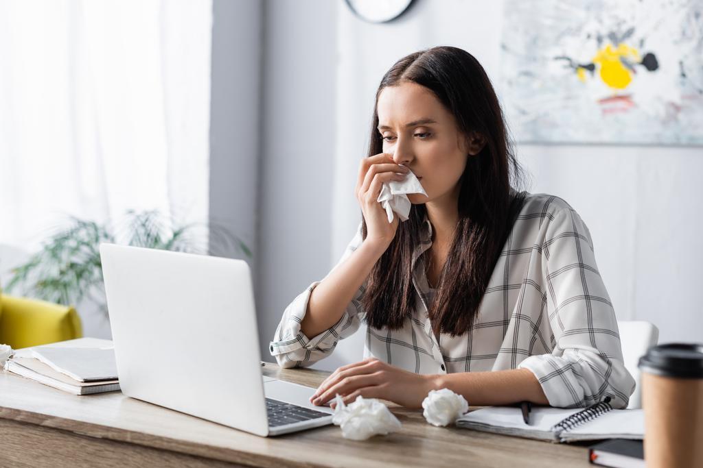 allergiás nő törlése orr papír szalvétával, miközben dolgozik laptop elmosódott előtérben - Fotó, kép