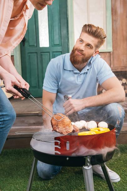 couple grilling meat and vegetables - Photo, Image