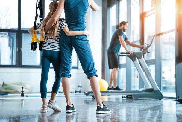 Woman with girl looking at handsome man workout on treadmill at gym - Photo, Image