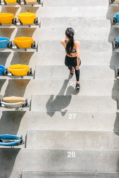 sportswoman running on stadium stairs - Photo, Image