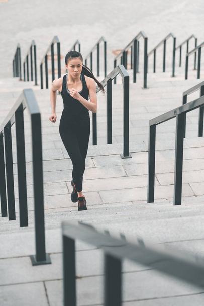 Sportswoman training on stadium stairs  - Photo, Image