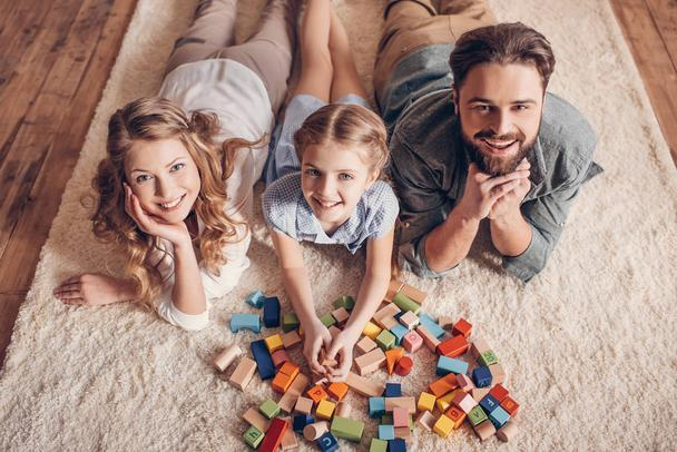 happy family playing with constructor and lying on floor at home - Photo, Image