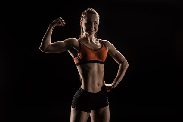 young smiling sportswoman flexing biceps - Photo, Image