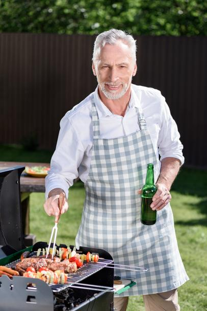 grey haired man preparing barbecue - Photo, Image