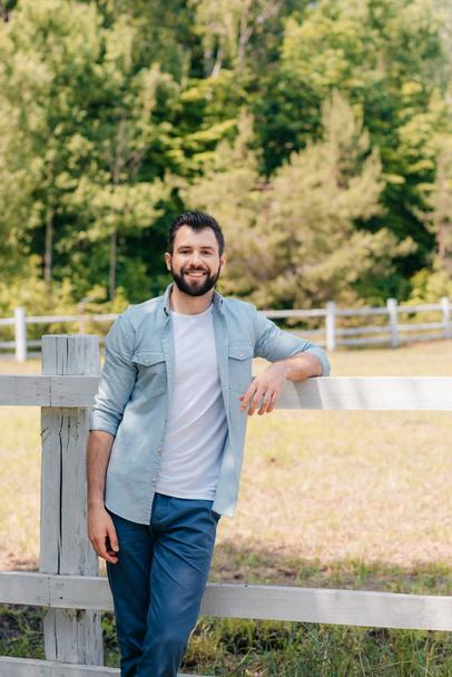 man standing at wooden fence - Photo, Image