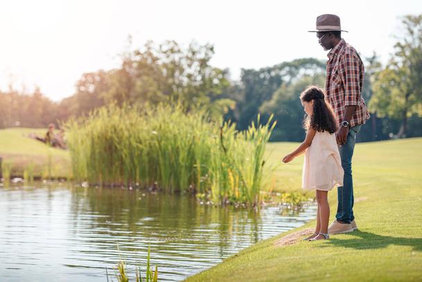 granddaughter and grandfather standing at lake - Photo, Image