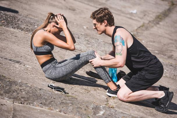 man helping sportive woman with training - Photo, Image