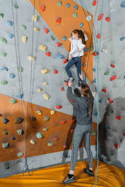 Little girl climbing wall with grips - Photo, Image