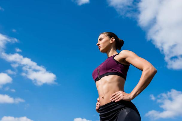 sporty woman in front of blue sky - Photo, Image