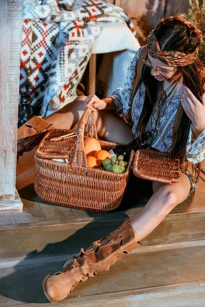 bohemian woman looking at basket of fruits - Photo, Image