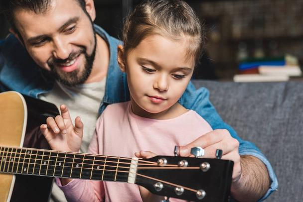 father learning daughter to play guitar - Photo, Image