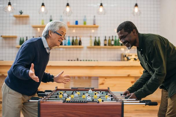 senior friends playing table football - Photo, Image