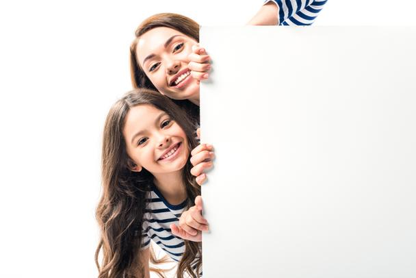Daughter and mother holding empty board - Photo, Image