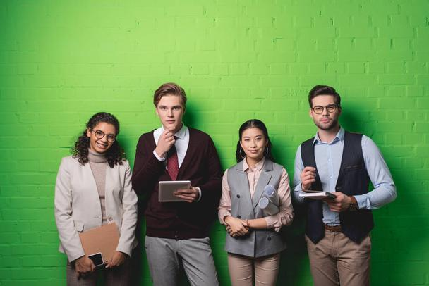 young multiethnic businesspeople with digital devices and documents standing in front of green wall - Photo, Image