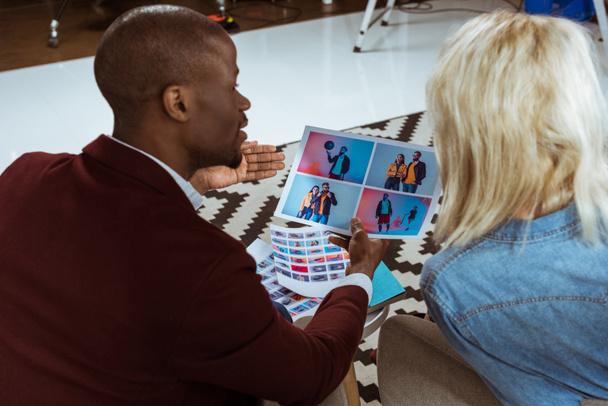 Rückseite der Fotografen, die ihr Portfolio gemeinsam im Büro auswählen - Foto, Bild