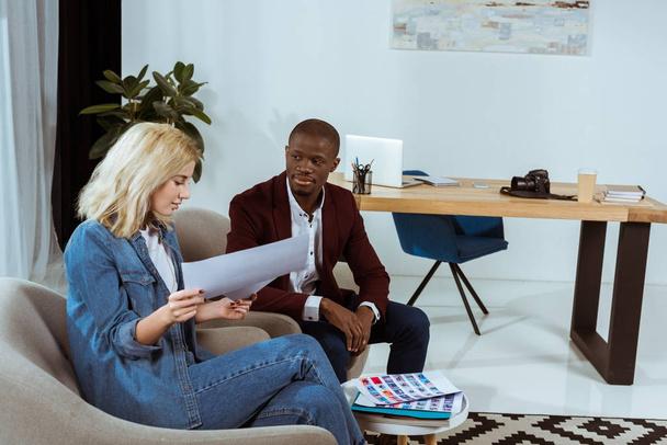 interrassische Fotografen, die gemeinsam Fotos auswählen, während sie im Büro in Sesseln sitzen - Foto, Bild