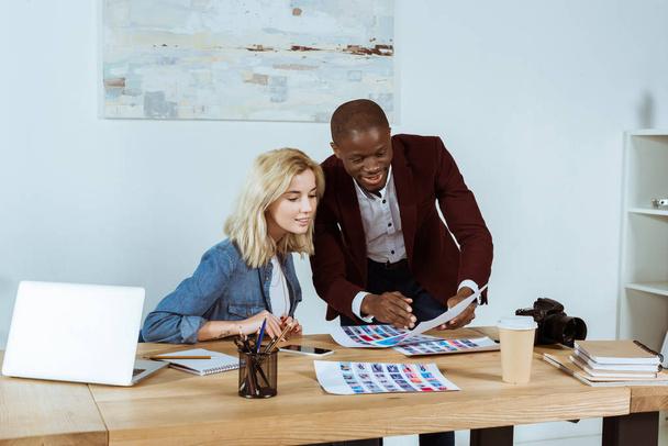 Portrait multiethnischer Fotografen, die ihre Mappe am Arbeitsplatz im Büro betrachten - Foto, Bild