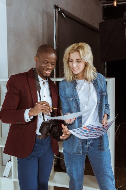 Porträt lächelnder multiethnischer Fotografen beim gemeinsamen Betrachten einer Mappe im Atelier - Foto, Bild