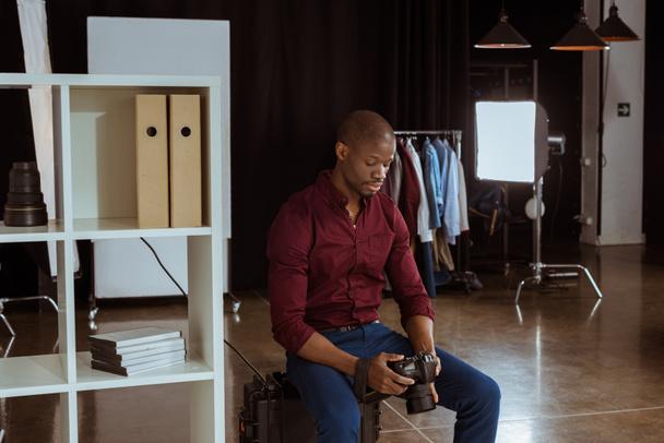 Porträt eines afrikanisch-amerikanischen Fotografen, der die Fotokamera in der Hand hält, während er im Studio Fotos auswählt - Foto, Bild