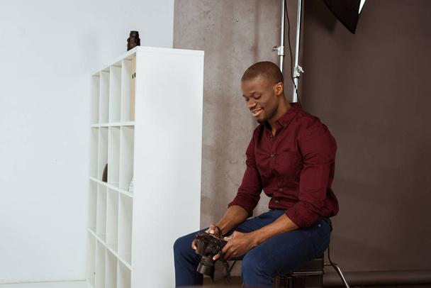 Seitenansicht eines lächelnden afrikanisch-amerikanischen Fotografen, der die Fotokamera in der Hand hält, während er im Studio Fotos auswählt - Foto, Bild