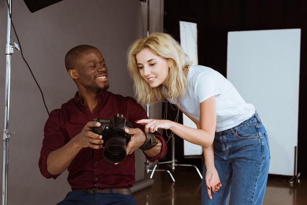 afrikanisch-amerikanischer Fotograf und kaukasisches Model beim gemeinsamen Fotoshooting im Studio - Foto, Bild