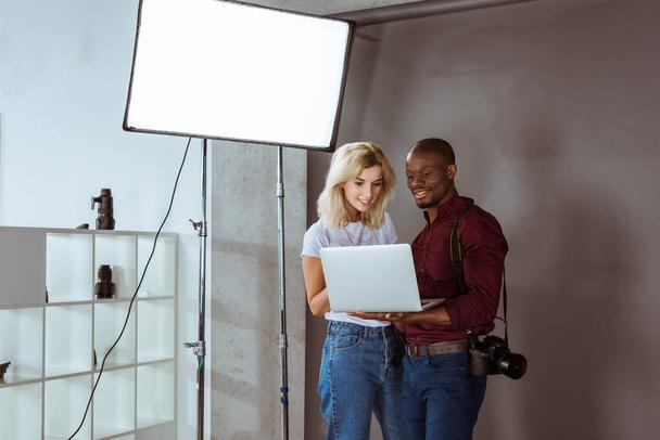 afrikanisch-amerikanischer Fotograf und kaukasisches Model beim gemeinsamen Fotoshooting im Studio bei der Auswahl von Fotos am Laptop - Foto, Bild
