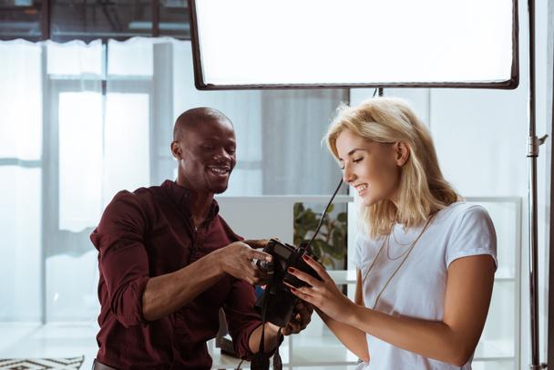 Porträt der fröhlichen afrikanisch-amerikanischen Fotografin und des kaukasischen Models beim gemeinsamen Fotoshooting im Studio - Foto, Bild