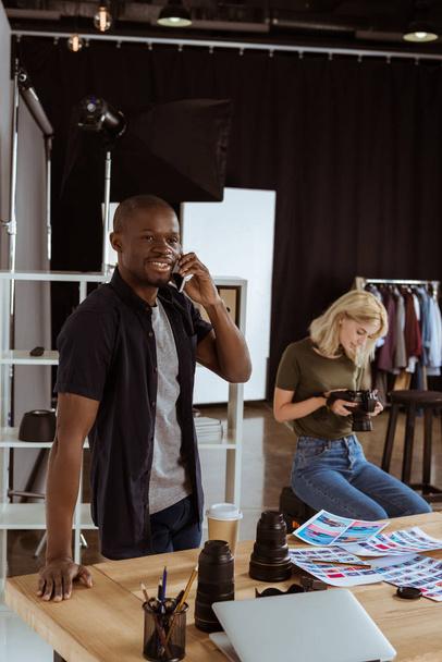 afikanisch-amerikanischer Fotograf spricht auf Smartphone, während kaukasischer Kollege Fotos im Studio auswählt - Foto, Bild