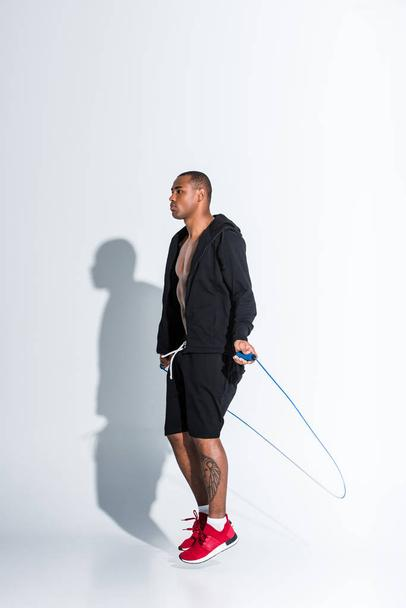 young african american sportsman exercising with skipping rope on grey - Photo, Image