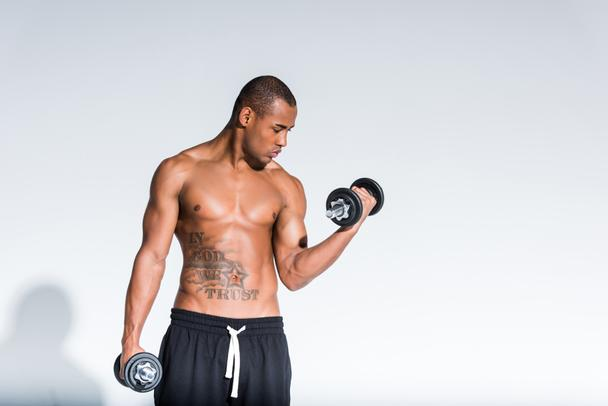 athletic young shirtless african american sportsman training with dumbbells isolated on grey  - Photo, Image