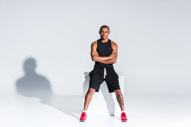young african american sportsman with crossed arms sitting and looking at camera on grey - Photo, Image