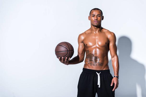 athletic shirtless african american man with basketball ball looking at camera on grey  - Photo, Image